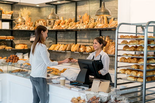 Latin American woman paying by card at the bakery while buying bread and pastries - small business concepts. Design on card is own design.