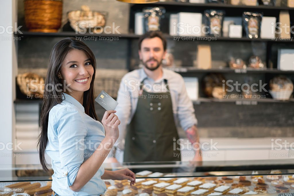 Woman paying by credit card at the bakery stock photo