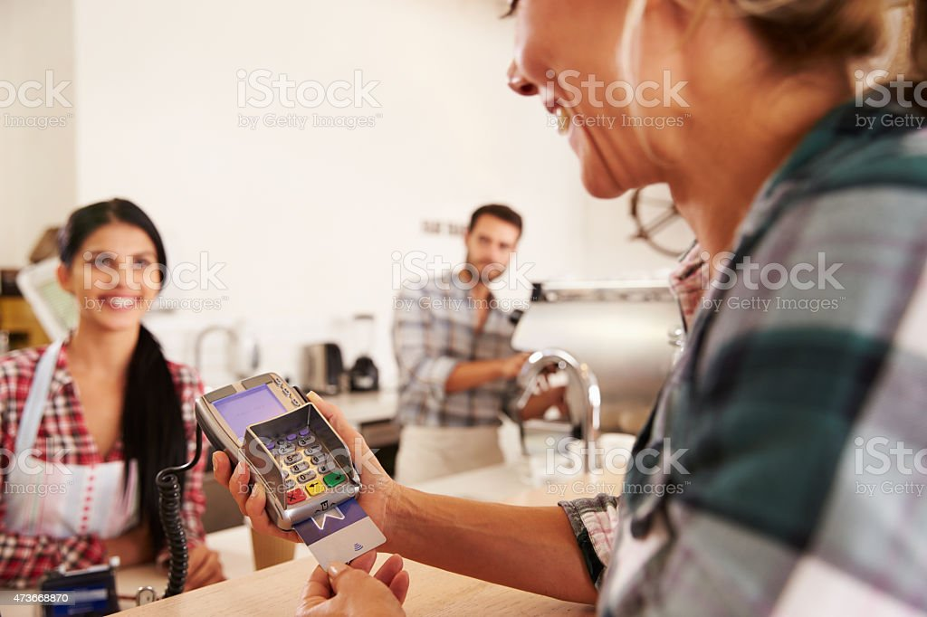 Woman paying by credit card in a cafe stock photo