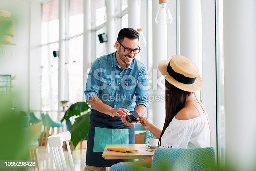 Woman paying by credit card in restaurant