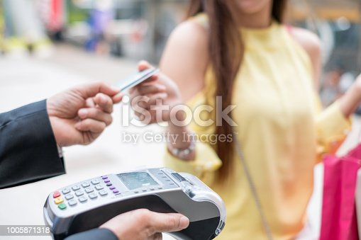 Close-up Woman paying credit card with payment terminal and cashier man