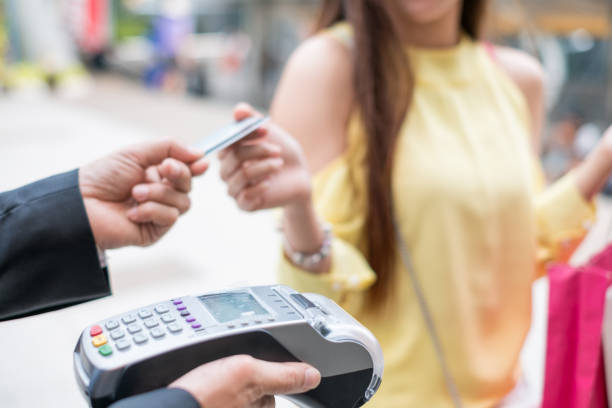Woman paying credit card with payment terminal and cashier man Close-up Woman paying credit card with payment terminal and cashier man smart card stock pictures, royalty-free photos & images