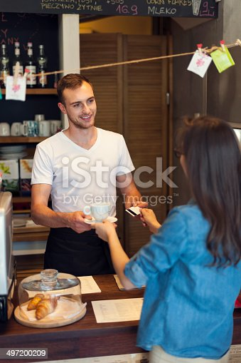 597640822istockphoto Woman paying for coffee by credit card 497200209