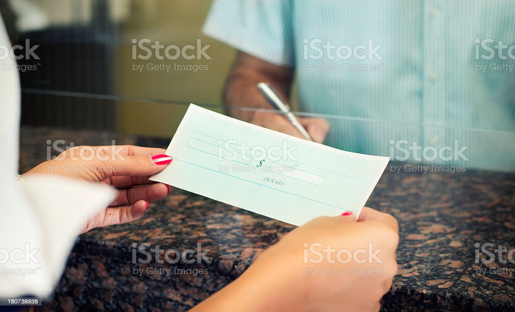 Woman paying in a check at the bank stock photo