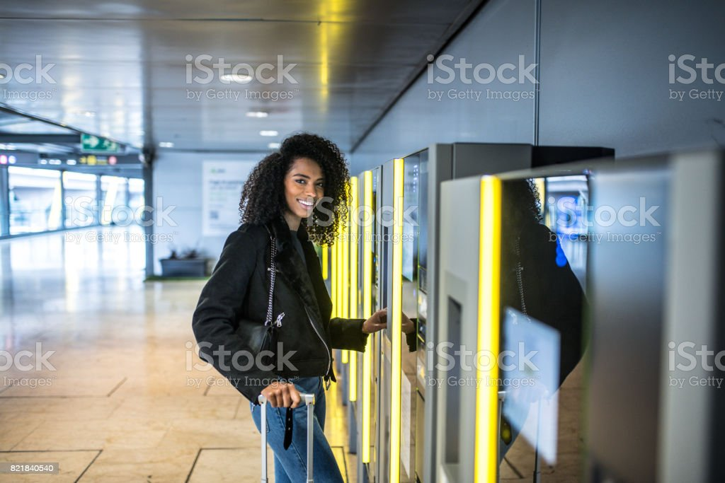 Woman paying in the parking Machine in the airport with a suitcase stock photo