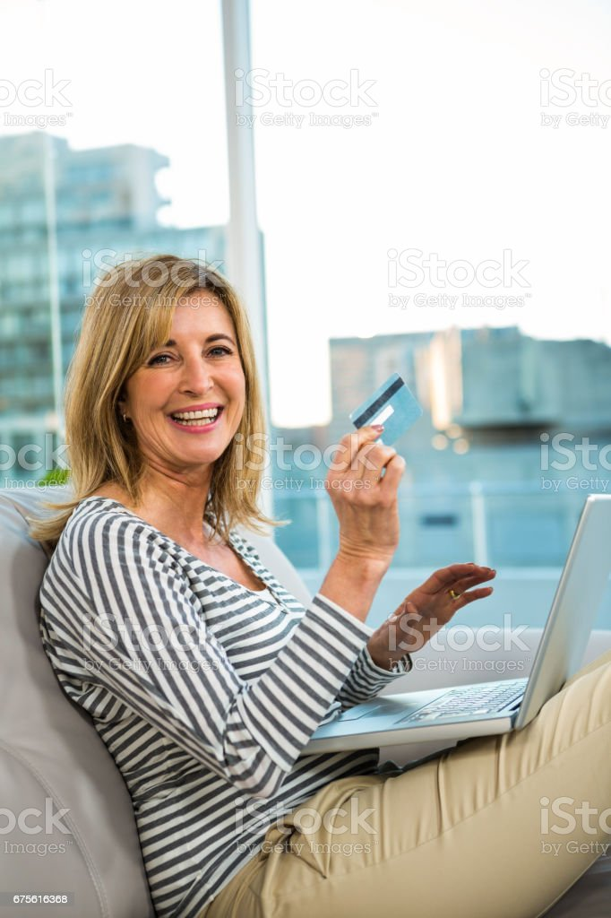 Woman paying on internet with her credit card stock photo