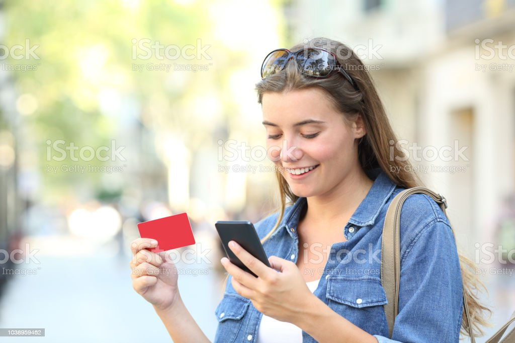 Woman paying online with a credit card outdoors - foto stock