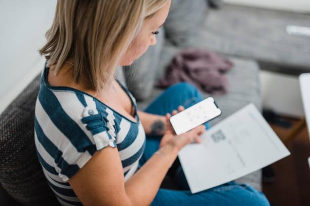 Frau, die Zahlung der Rechnungen und benutze ein Laptop auf dem sofa – Foto