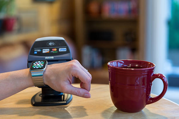 Woman Paying using Apple Watch and Electronic Reader stock photo