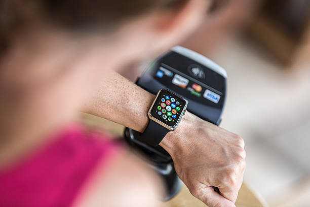 donna pagando con apple watch e lettore elettronico - apple computers foto e immagini stock