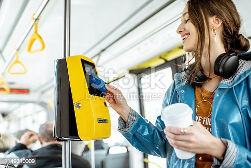 Woman paying conctactless with bank card for the public transport in the tram
