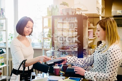 istock Woman paying with credit card in a cafe 687227800