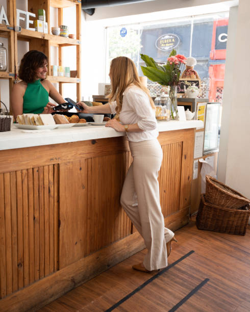 Woman paying with mobile phone for coffee in Buenos Aires café, contact less payment stock photo