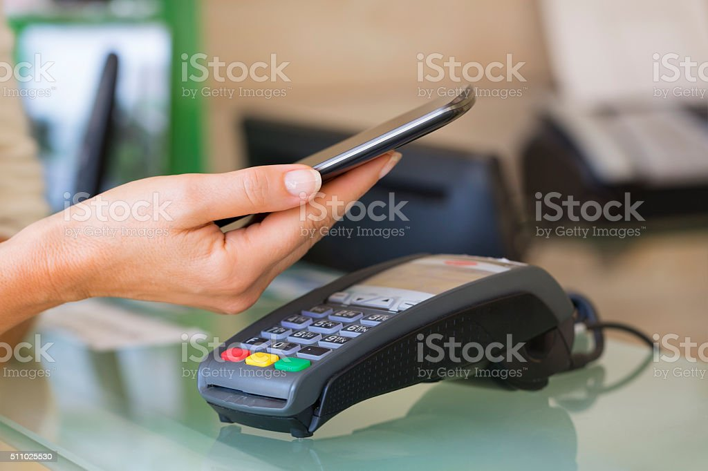 Woman paying with NFC technology on mobile phone, beautician, stock photo