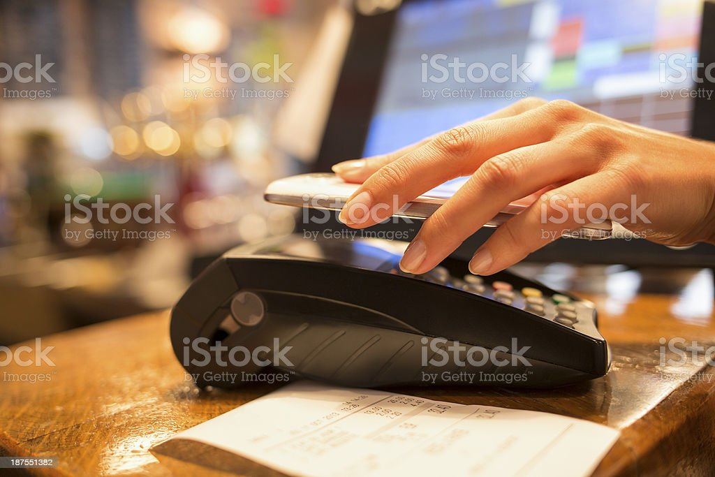 Woman paying with NFC technology on mobile phone in restaurant royalty-free stock photo