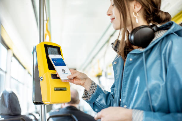 woman paying with phone for the public tarnsport - paying with card contactless imagens e fotografias de stock
