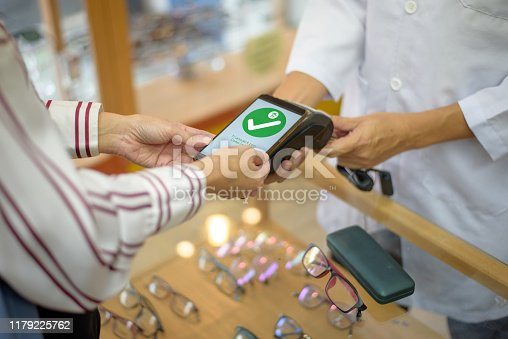 istock Woman Paying With Smartphone 1179225762