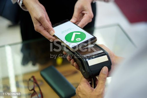 istock Woman Paying With Smartphone 1179225763