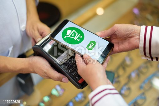 istock Woman Paying With Smartphone 1179226291