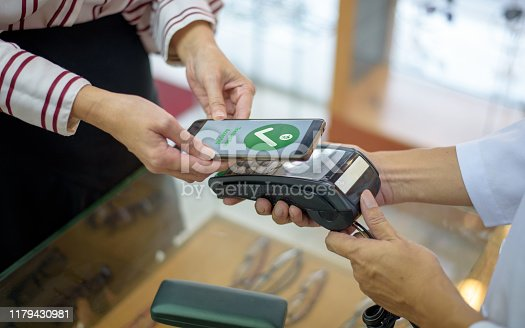istock Woman Paying With Smartphone 1179430981