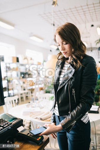 istock Woman Paying With Smartphone 814541218