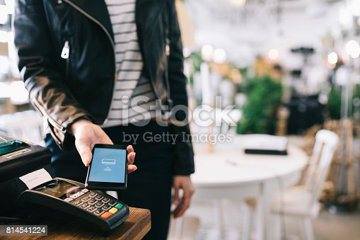istock Woman Paying With Smartphone. 814541224