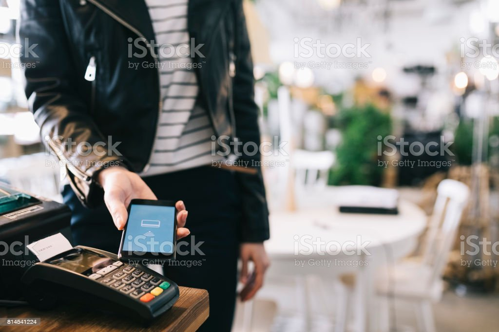 Woman Paying With Smartphone. stock photo