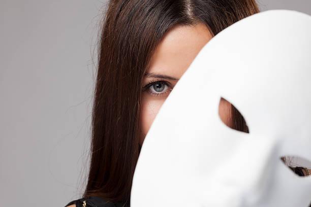 Woman peeking behind mask stock photo