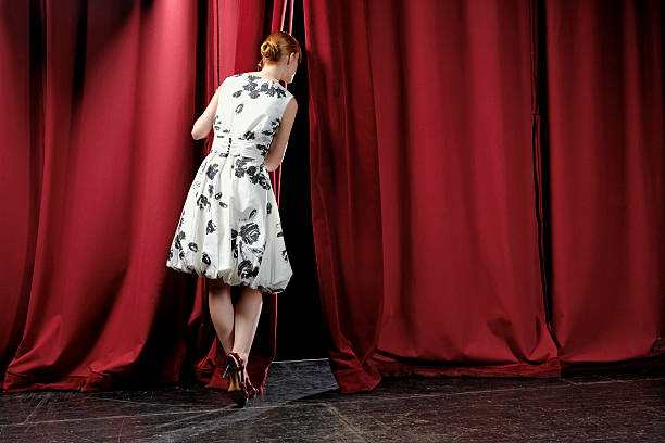 Woman peeking between stage curtains, rear view stock photo