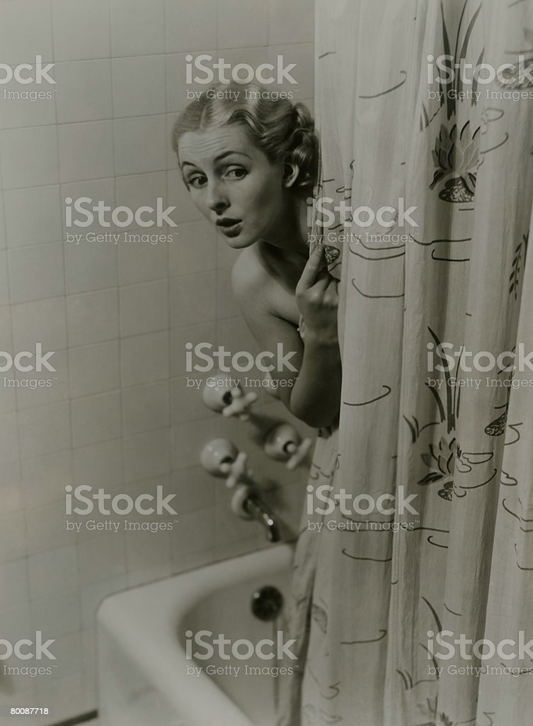 Woman peeking from behind shower curtain 免版稅 stock photo