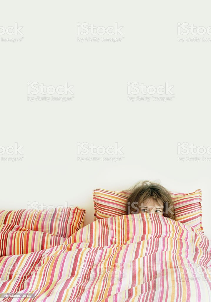 Woman peeking from duvet on bed royalty-free stock photo