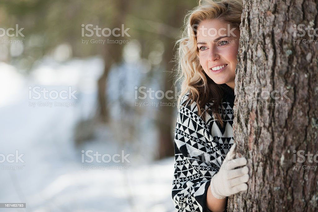 Woman peeking out from behind tree royalty-free stock photo