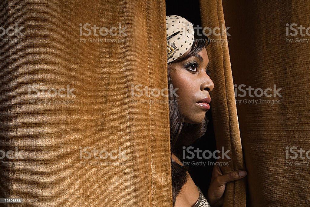 Woman peeking through curtains 免版稅 stock photo