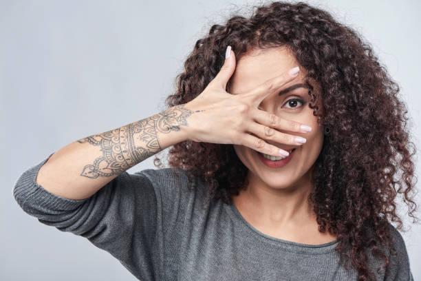 frau spähen durch finger - lausbub tattoo stock-fotos und bilder