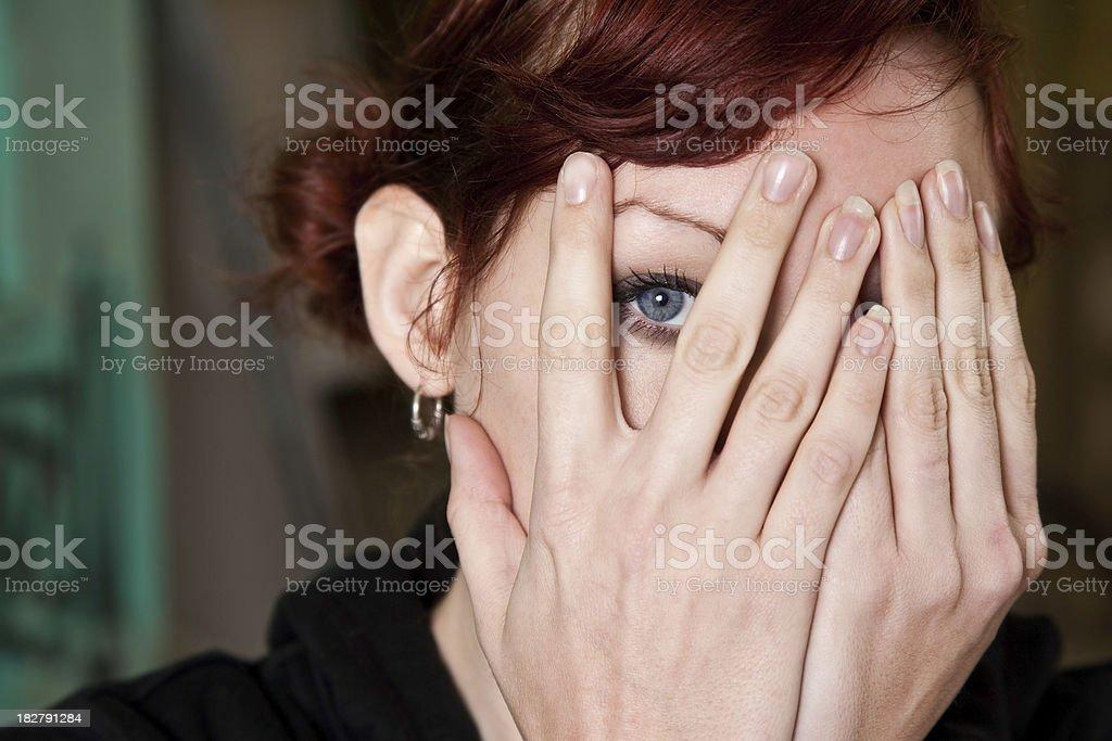 Woman Peeking Through Her Hands stock photo