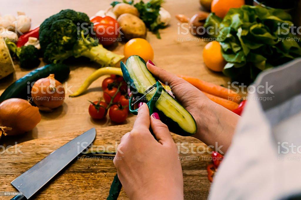 Woman peeling a cucumber stock photo