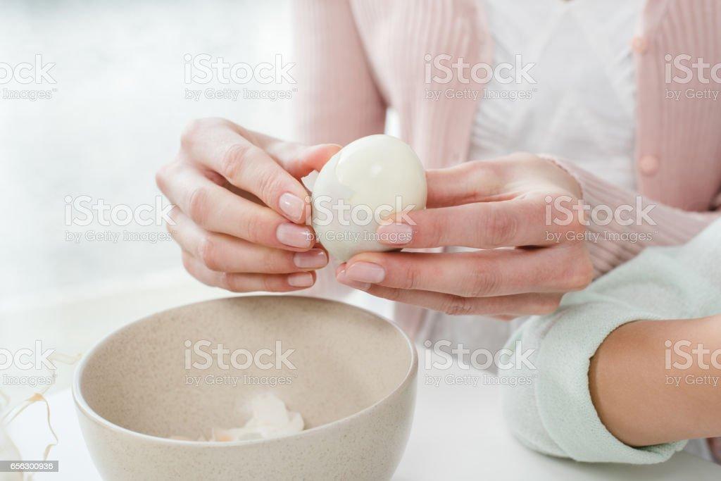 Woman peeling boiled egg stock photo