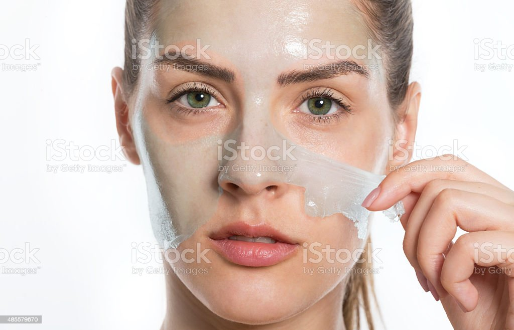 Woman peeling off face mask stock photo