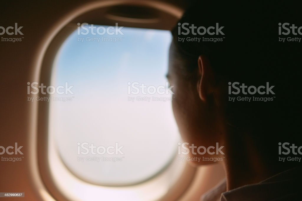 Woman peering out the window of an airplane royalty-free stock photo