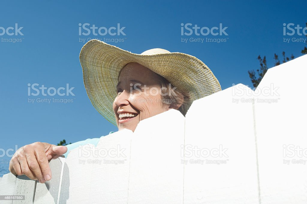 Woman Peering Over Garden Fence stock photo