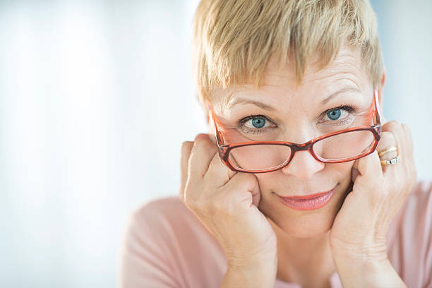 Woman Peering Over Her Eyeglasses Close-up portrait of mature woman peering over her eyeglasses raised eyebrows stock pictures, royalty-free photos & images