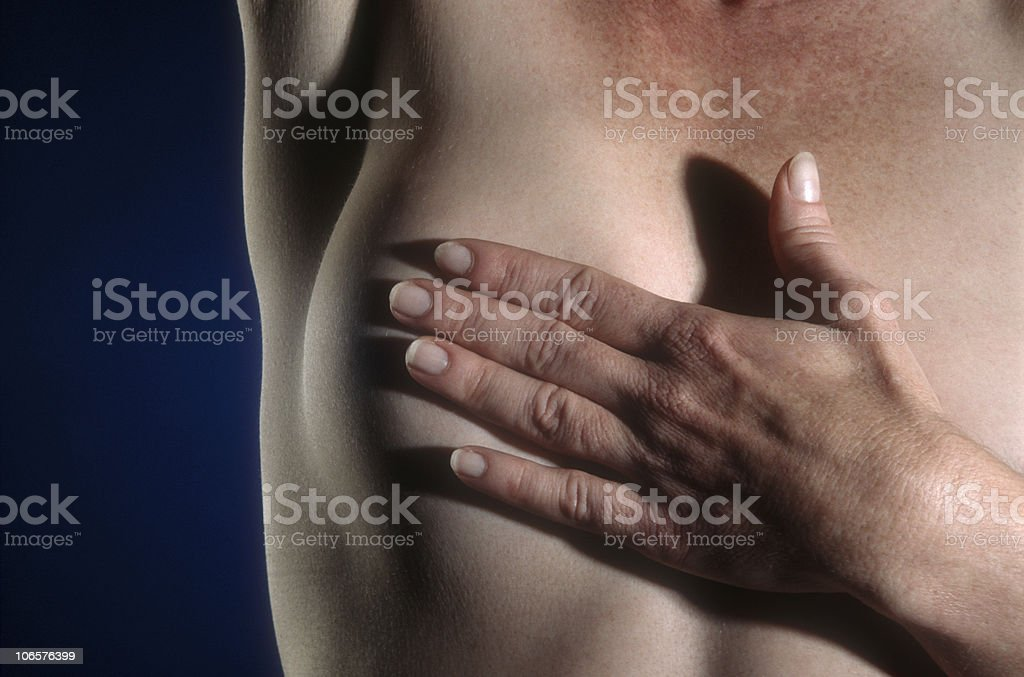 Woman performing a breast exam with her hand  stock photo
