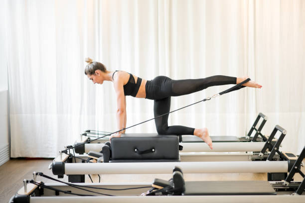 woman performing a pilates diagonal stabilisation - metodo pilates foto e immagini stock