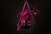 Full body side view of flexible young female aerial dancer doing splits on hanging ribbons against black background