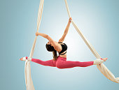 Sporty woman doing exercise with elastics, aerial silk ribbons.