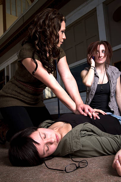 Woman performing CPR on an unconscious woman stock photo