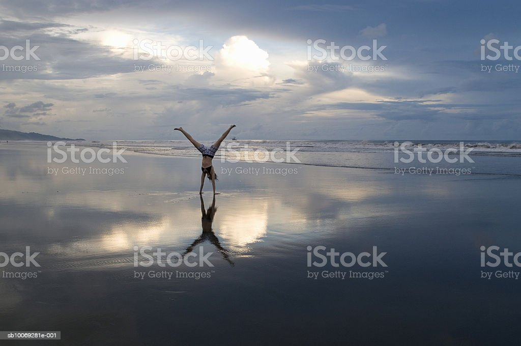 Woman performing handstand on beach at sunset royalty-free stock photo