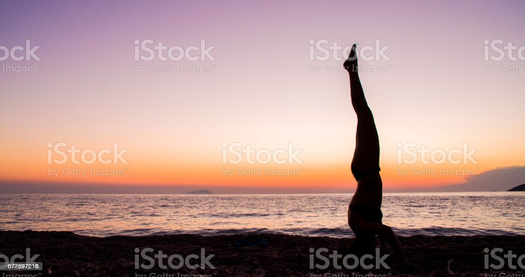 Woman performing headstand by sea during sunset royalty-free stock photo