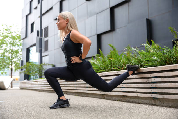 Woman Performing Lunges Workout for Thighs and Glute Outdoor in the City stock photo