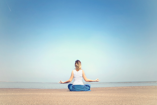 Woman Performing Relaxation And Meditation Exercises At The Sea Stock Photo - Download Image Now